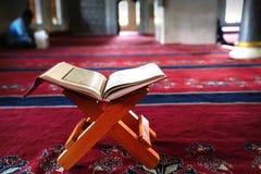 Heilige Koran op tribune op rood tapijt stock afbeelding