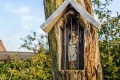 Heilige Mary-Statuette in einer Nische schnitzte heraus in einem alten Baum Lizenzfreie Stockbilder
