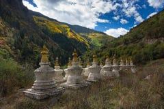 Heilige Pagoden im tibetanischen Tempel mit buntem Wald auf Berg Stockbild