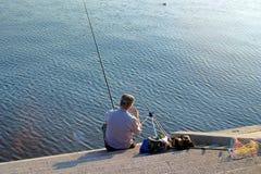 Heilige Petersburg, Rusland - Augustus 16, 2018: De visser op de waterkant zet het aas op de staaf royalty-vrije stock afbeeldingen