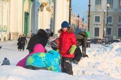 Heilige-Petersburg, RUSLAND - 16 die Januari 2016, Kinderen op de sneeuw op het Paleisvierkant spelen, de winter, dageraad Royalty-vrije Stock Foto's