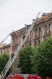 Heilige Petersburg, Rusland, op de ochtend van 13 September, 2017 De brandbestrijders doven een grote brand op het dak van a Stock Foto