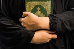 Heilige Schrift des Korans in der Hand - der Moslemfrau des Korans der Moslem-(allgemeines Einzelteil aller Moslems) in der Hand stockbilder