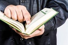 Heilige Schrift des Korans in der Hand - von Moslems (allgemeines Einzelteil aller Moslems) lizenzfreie stockfotos