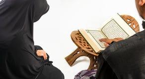 Heilige Schrift des Korans in der Hand - von Moslems (allgemeines Einzelteil aller Moslems stockfotos