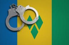 Heilige Vincent en van de Grenadinesvlag en politie handcuffs Het concept misdaad en inbreuken in het land royalty-vrije stock fotografie
