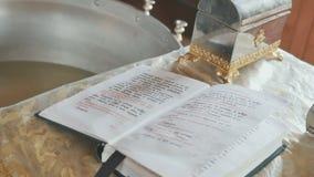 Heiliger Guss mit Weihwasser, die Bibel mit Gebet bei Tisch in der Kirche stock footage