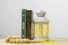 Heiliger Quran, Rosenbeet und Laterne auf Holztisch, mit weißem bric Stockbild