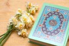 Heiliger Quran- und Narzissenblumenstrauß auf hölzernem Hintergrund Stockbilder