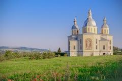 Heiliger Tempel auf einem Hügel mit Mohnblumen gegen einen klaren Himmel Lizenzfreies Stockbild