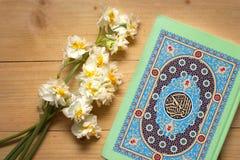 Heiliges Quranbuch und -narzissen auf dem hölzernen Hintergrund ramadan Stockfotos
