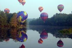 Heißluftballone über Wasser Lizenzfreie Stockfotos