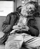 Heimatloser Kerl, der auf einer Bank schläft Stockbilder