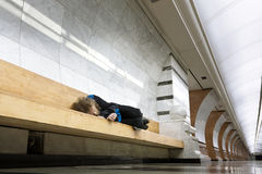 Heimatloser Mann, der auf der Bank schläft Stockbild