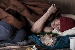 Heimatloser Mann, der auf der Straße schläft lizenzfreies stockbild