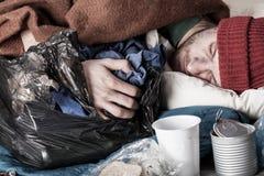 Heimatloser Mann, der auf der Straße schläft Stockbilder