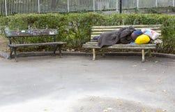 Heimatloser Mann, der auf einer Bank schläft Lizenzfreies Stockbild