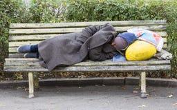 Heimatloser Mann, der auf einer Bank schläft Lizenzfreie Stockfotografie