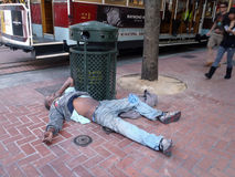 Heimatloser Mann schläft auf dem Boden Stillstehen Lizenzfreies Stockfoto