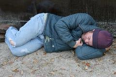 Heimatloser Mann - schlafend durch Dumpster Stockfotos