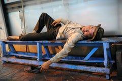 Heimatloser Mann schläft auf der Straße Stockbild