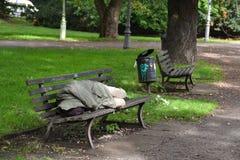 Heimatloses Schlafen auf einer Parkbank Stockfotografie