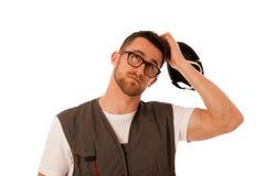 Heimwerker in der Arbeitskleidung, die auf dem Kopf, oben schauend, thinki verkratzt Stockbild