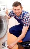 Heimwerker in der blauen Uniform, die eine Waschmaschine repariert Stockbild