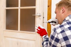 Heimwerker, der die Tür mit Schraubenzieher repariert Stockfotos
