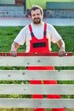 Heimwerker, der einen Bretterzaun errichtet Lizenzfreie Stockbilder