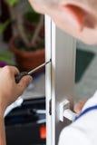 Heimwerker, der Fenster mit Schraubenzieher repariert lizenzfreie stockfotos