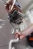 Heimwerker, der GasWarmwasserbereiter repariert Stockfoto