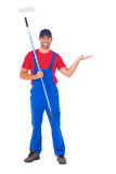 Heimwerker mit der Farbenrolle, die in seiner Palme auf weißem Hintergrund sich darstellt Stockfoto