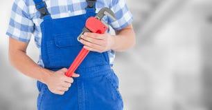 Heimwerker mit rotem Schlüssel gegen undeutliche graue Treppe Stockbild