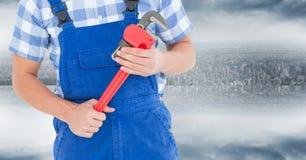Heimwerker mit rotem Schlüssel gegen undeutliche Skyline Stockbilder