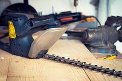Heimwerkerwerkzeug auf dem Tisch verschüttet mit Heckenschere Lizenzfreies Stockfoto