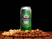 Heineken beer. ZAGREB , CROATIA - JANUARY 24 ,2014 :  Beer can on black background, Heineken with peanuts and huzelnuts on the table, product shot Stock Photography
