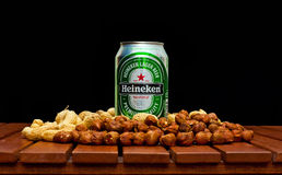 Heineken beer. ZAGREB , CROATIA - JANUARY 24 ,2014 :  Beer can on black background, Heineken with peanuts and huzelnuts on the table, product shot Stock Photo