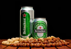 Heineken beer. ZAGREB , CROATIA - JANUARY 24 ,2014 :  Beer cans on black background, Heineken with peanuts and huzelnuts on the table, product shot Royalty Free Stock Image