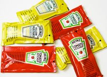Ketchup and mustard from Heinz brand in sachets. Heinz brand ketchup and mustard envelopes isolated on white background in macro view royalty free stock photo