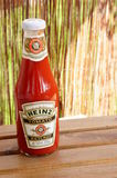Heinz Ketchup. Large bottle of Heinz ketchup standing on a wooden table stock photo