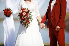 Heirat in der Art Marsalafarbe Braut- und Bräutigamhändchenhalten am Altar Lizenzfreies Stockbild