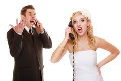 Heirat. Verärgerte Braut und Bräutigam, die am Telefon spricht Stockbild