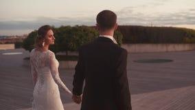 Heiraten Sie eben liebevollen Paarweg und -uhr zum Sonnenuntergang stock footage