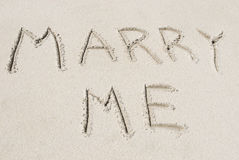 Heiraten Sie mich geschrieben in den Sand Stockfotografie