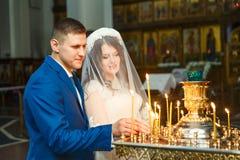 Heiratend in der Kirche, beleuchten Jungvermählten Kerzen in der Kirche lizenzfreie stockfotografie