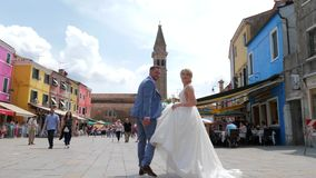 Heiratend in Europa, gehen glückliche Braut und Bräutigam um die gedrängte Stadt auf backround von bunten Häusern und von berühmt stock video