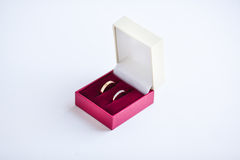 Heiratende goldene Ringe im roten Kasten auf Weiß stockbilder