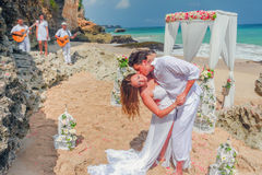 Heiratende schöne Paare, die gerade geheiratet werden und am Strand geküsst sind Lizenzfreie Stockfotografie