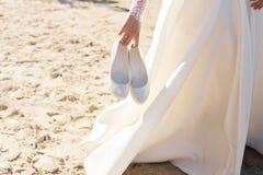 Heiratende warme weiße Schuhe in Braut ` s Händen auf dem Strand Lizenzfreies Stockbild